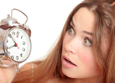 Unhappy girl waking up too late and looking at the alarm clock. Isolated over white background.